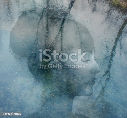 Double exposure with a woman sitting from the top in a frozen lake where the trees are reflecting. ArtworkDouble exposure with a woman sitting from the top in a frozen lake where the trees are reflecting. Artwork