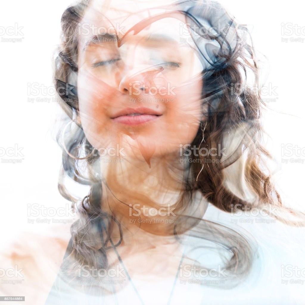 Double exposure of a young happy natural beauty with wavy hair and layers of a smoky swirling texture stock photo
