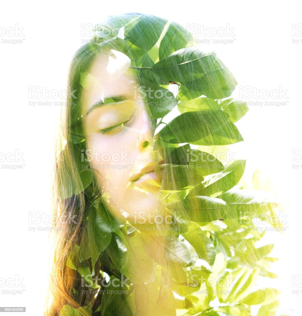 Double exposure of a young natural beauty combined with bright shining tropical leaves stock photo