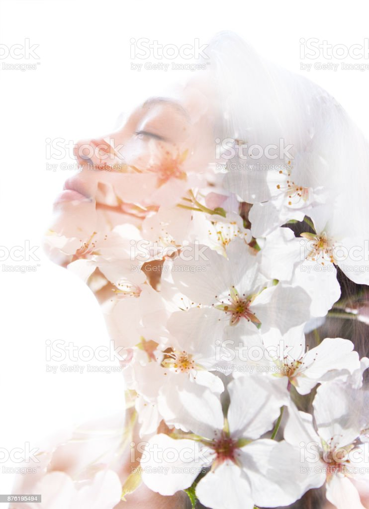 Double exposure of a young natural beauty relaxing and softly tilting her head back as her forehead and hair combines perfectly with delicate fragrant white flowers stock photo