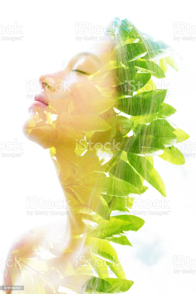 Double exposure of a young natural beauty relaxing and softly tilting her head back as her forehead and hair combines perfectly with bright tropical leaves 'n stock photo