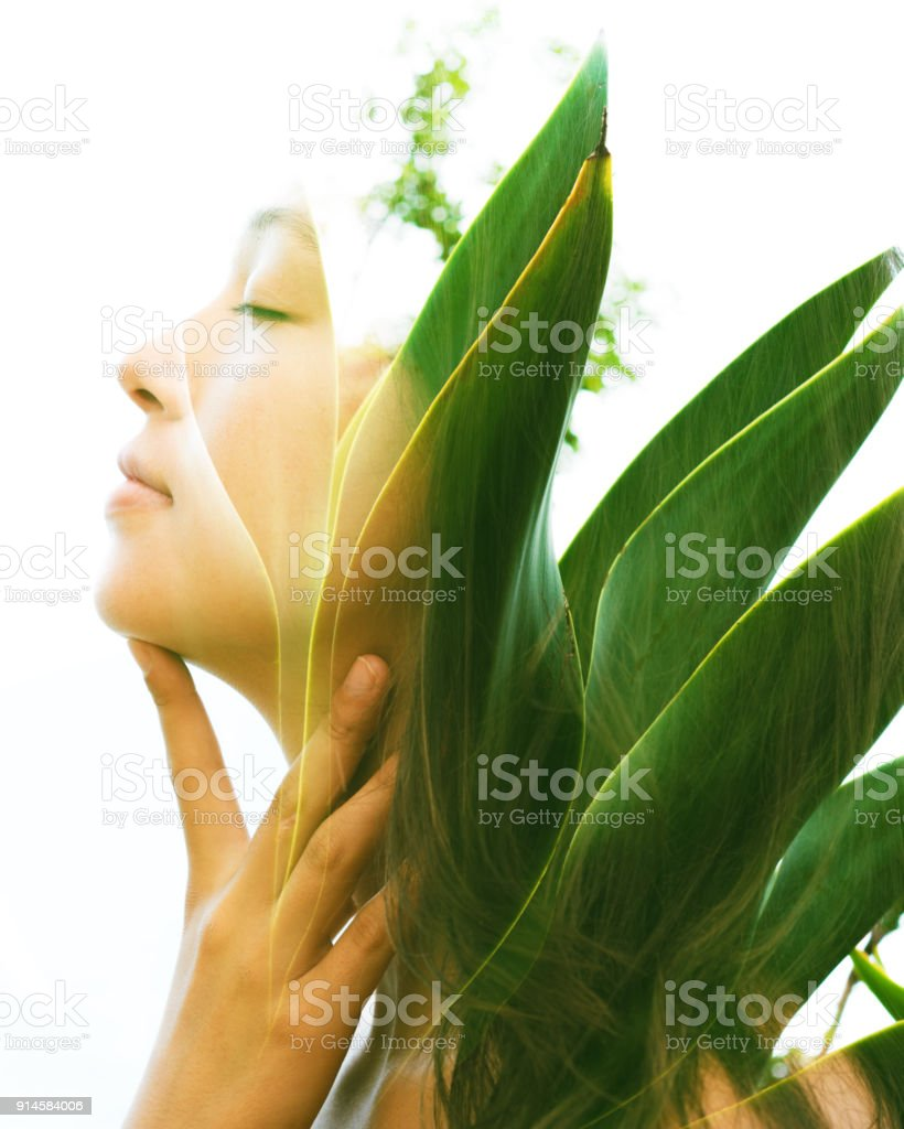 Double exposure of a young natural beauty with closed eyes, relaxing and softly touching her throat and chin as her face and hair combine perfectly with bright tropical leaves stock photo