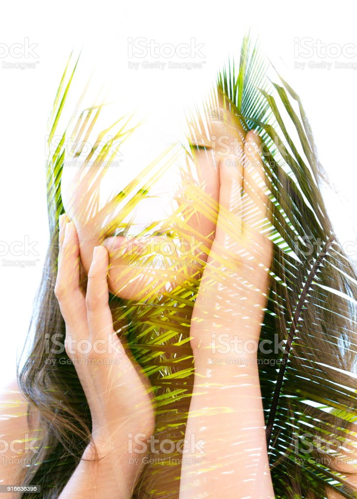 Double exposure of a young natural beauty with closed eyes, relaxing and softly touching her visage and chin as her face and hair combine perfectly with bright tropical leaves stock photo