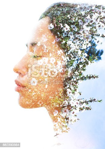 istock Double exposure of a young natural beauty with strong sexy features dissolves into a photograph of delicately fragrant white flowers 882390564