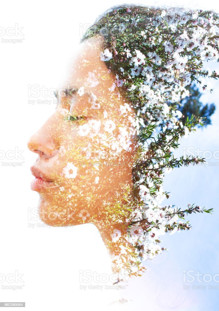 Double exposure of a young natural beauty with strong sexy features dissolves into a photograph of delicately fragrant white flowers - foto stock
