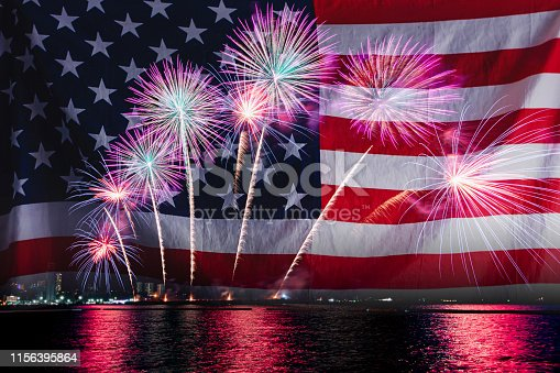 istock Double exposure of Amazing beautiful colorful fireworks display on celebration night with USA flag, showing on the sea beach with multi color of reflection on water. 4th July Independence day concept. 1156395864