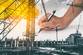 istock Double exposure of  architect working on blueprint with construction site. 845537400