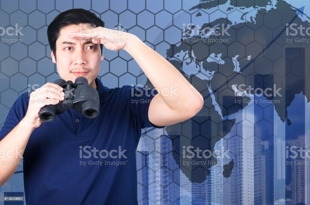 Double exposure of Asian investor with binoculars. Over abstract urban background and world map, furnished by NASA. stock photo