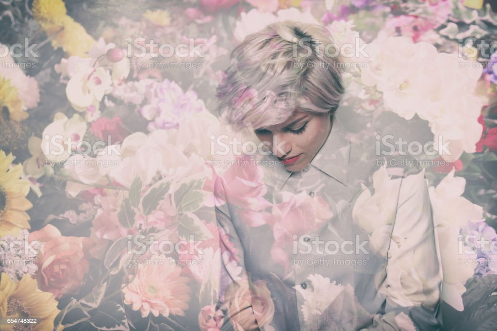 Double exposure of beautiful thoughtful girl portrait and colorful flowers stock photo