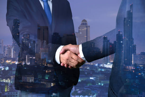 double exposure of business handshake for successful of investment deal and city night background, teamwork and partnership concept. - double exposure стоковые фото и изображения