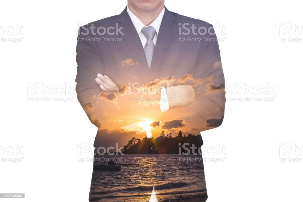 Double exposure of business man arms crossed and sunrise on the beach in the morning as business, leadership and nature concept. stock photo