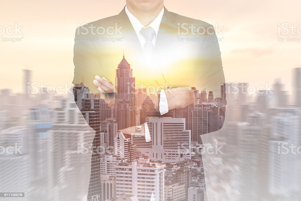 Double exposure of business man arms crossed, cityscape and sunset stock photo