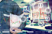 istock Double exposure of  business man or Engineer holding helmet with stock trading room and stock trading chart background for investment business concept. 1153053183