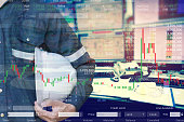 istock Double exposure of  business man or Engineer holding helmet with stock trading room and stock trading chart background for investment business concept. 1153436769