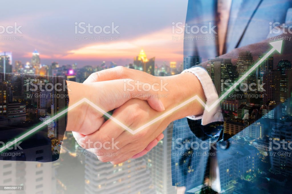Double exposure of businessman and businesswoman handshake make graph growth with city of business in blue tone background royalty-free stock photo