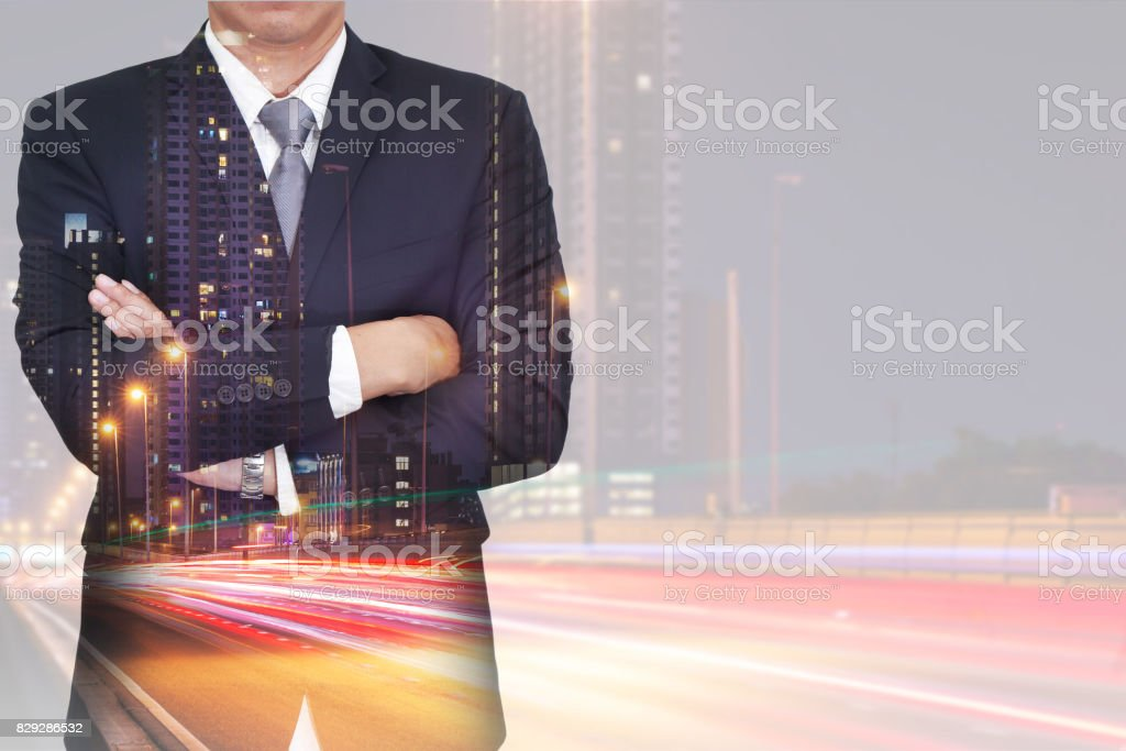 Double exposure of businessman arms crossed, light trails on street stock photo