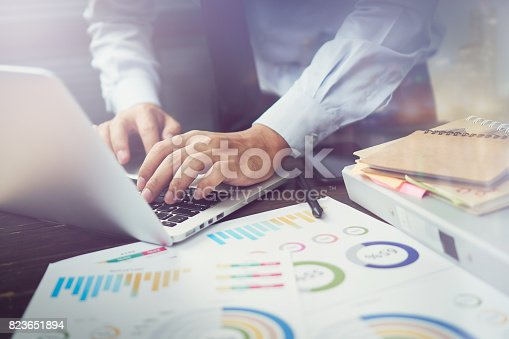 istock double exposure of businessman hand working laptop on wooden desk in office in morning light. The concept of modern work with advanced technology. vintage effect 823651894