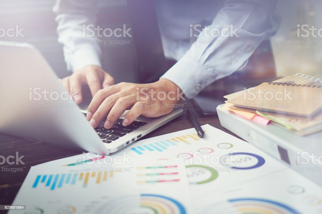 double exposure of businessman hand working laptop on wooden desk in office in morning light. The concept of modern work with advanced technology. vintage effect stock photo