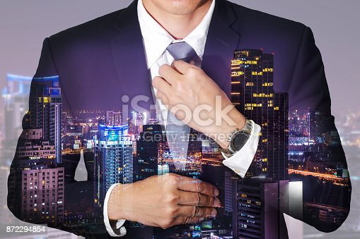 istock Double exposure of businessman held necktie dress to look good and night cityscape as get ready of business concept. 872294854