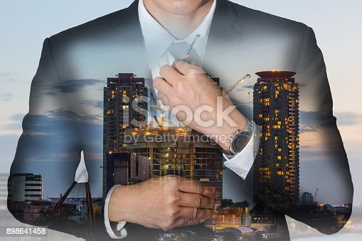istock Double exposure of businessman held necktie dress to look good, construction crane and building in the evening or twilight as business and industrial concept. 898641458