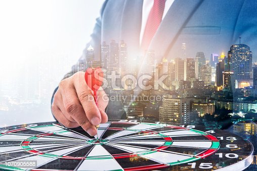 istock Double exposure of Businessman holding arrow on dart board with withe blur city night background, achieve target to victory concept 1070905588