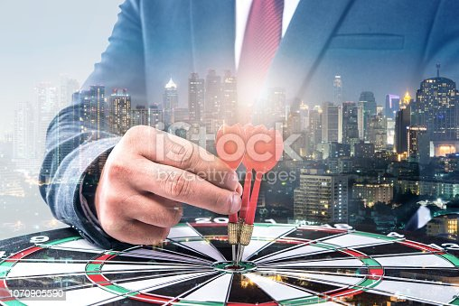 istock Double exposure of Businessman holding arrow on dart board with withe blur city night background, achieve target to victory concept 1070905590
