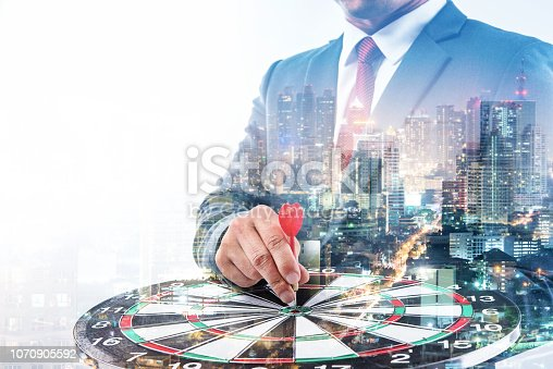 istock Double exposure of Businessman holding arrow on dart board with withe blur city night background, achieve target to victory concept 1070905592