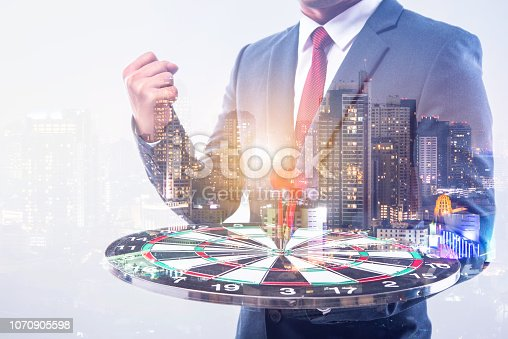 istock Double exposure of Businessman holding arrow on dart board with withe blur city night background, achieve target to victory concept 1070905598