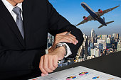 Double exposure of businessman look the watch about taketime, airplane takeoff in morning city or urban at blue day as business, meeting, transportation, Appointment and travel concept.
