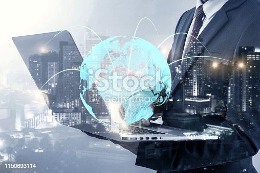 Double exposure of businessman using laptop show globe simulation at office with city night background, digital network connection concept