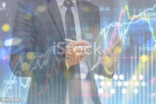 860389678 istock photo Double exposure of businessman using smart tablet over the soft screen of stock market background, business trading concept 815420252