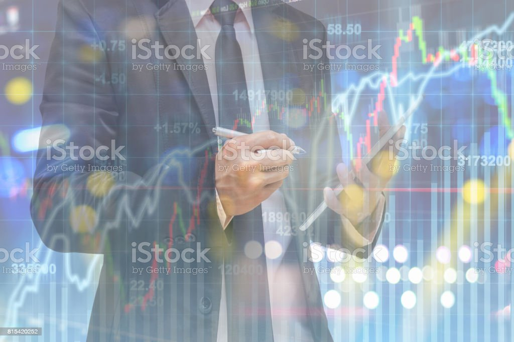 Double exposure of businessman using smart tablet over the soft screen of stock market background, business trading concept stock photo
