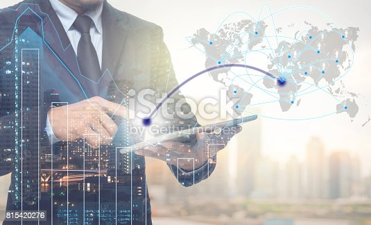 611747524istockphoto Double exposure of businessman using tablet for connection with cityscape and financial graph on blurred building background,Business Trading concept,Elements of this image furnished by NASA 815420276