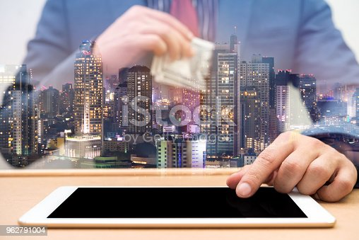 917307226istockphoto Double Exposure of businessman using tablet with city night 962791004