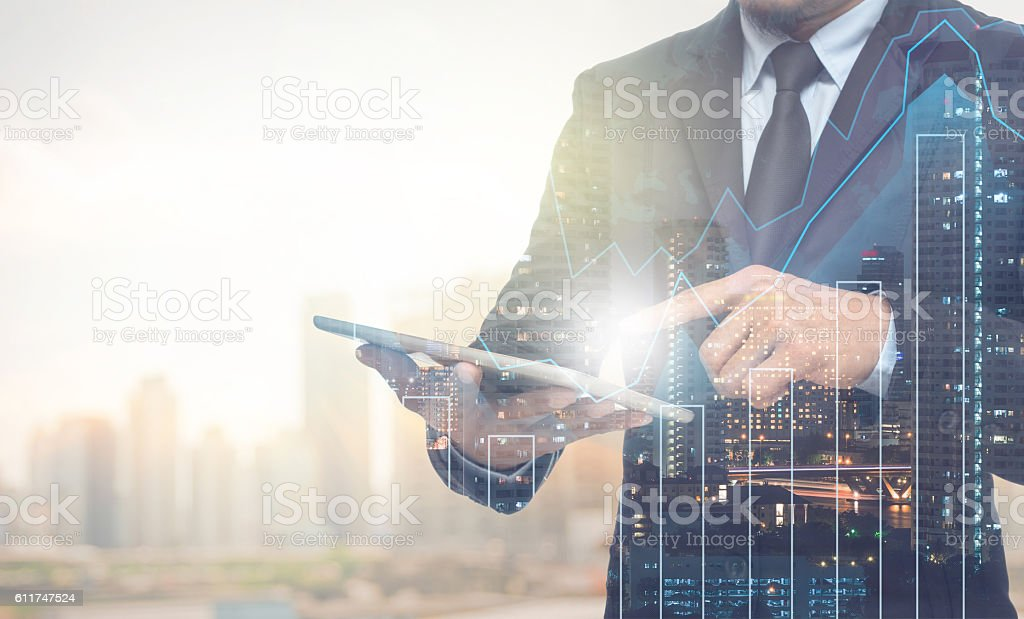Double exposure of businessman using the tablet with cityscape Double exposure of businessman using the tablet with cityscape and financial graph on blurred building background, Business Trading concept Adult Stock Photo