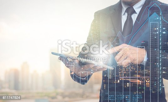 istock Double exposure of businessman using the tablet with cityscape 611747524