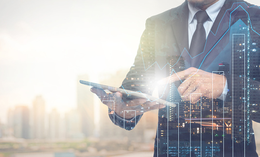 Double Exposure Of Businessman Using The Tablet With Cityscape Stock Photo - Download Image Now