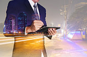 istock Double exposure of businessman working with tablet, urban,city and street at night as Communication, telecommunication and Technology concept 865976230