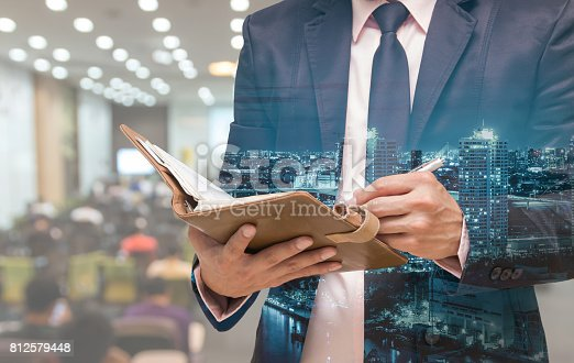 821463698 istock photo Double exposure of Businessman writing the note book on the Abstract blurred photo of conference hall or seminar room with attendee background 812579448