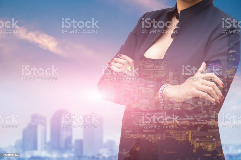 Double exposure of businesswoman arms crossed for success story and city background. stock photo