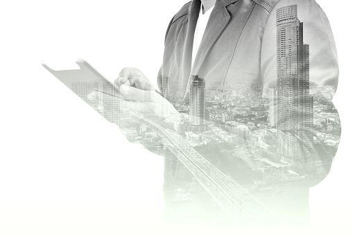 635942136 istock photo Double exposure of city and Businessman use Tablet device 505968136