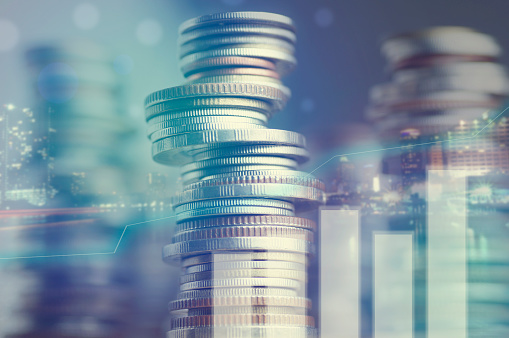 istock Double exposure of city and graph on rows of coins 645732556