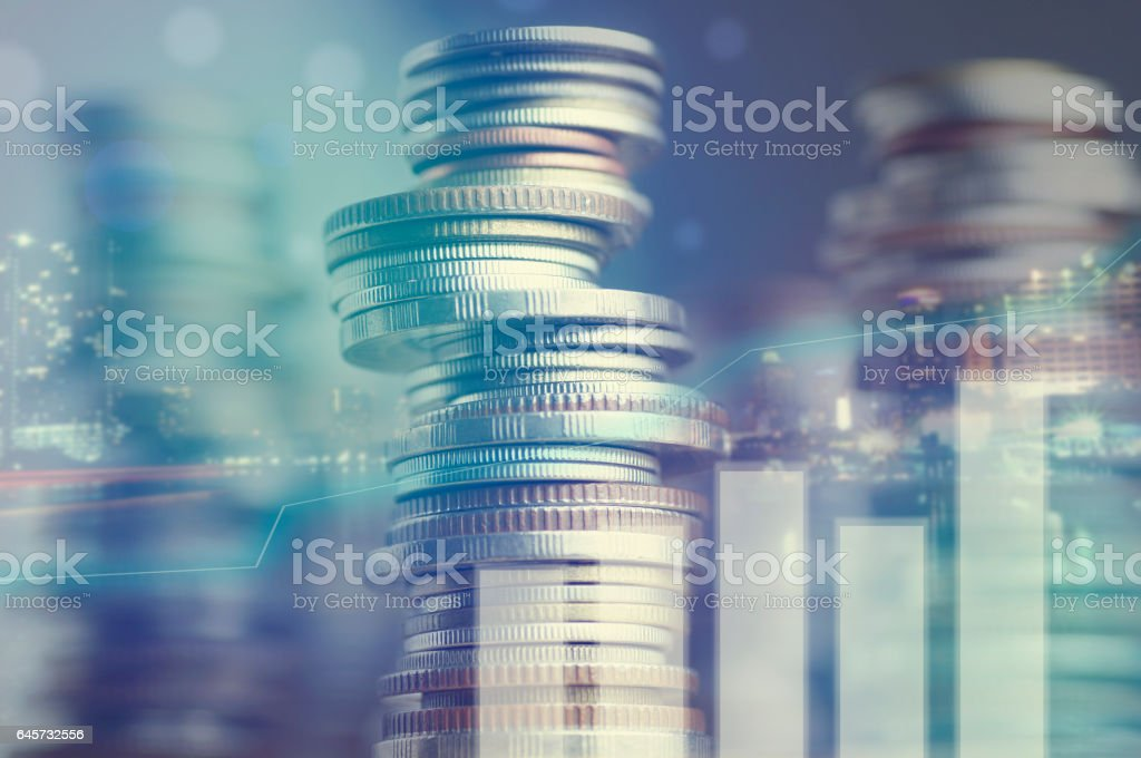 Double exposure of city and graph on rows of coins stock photo