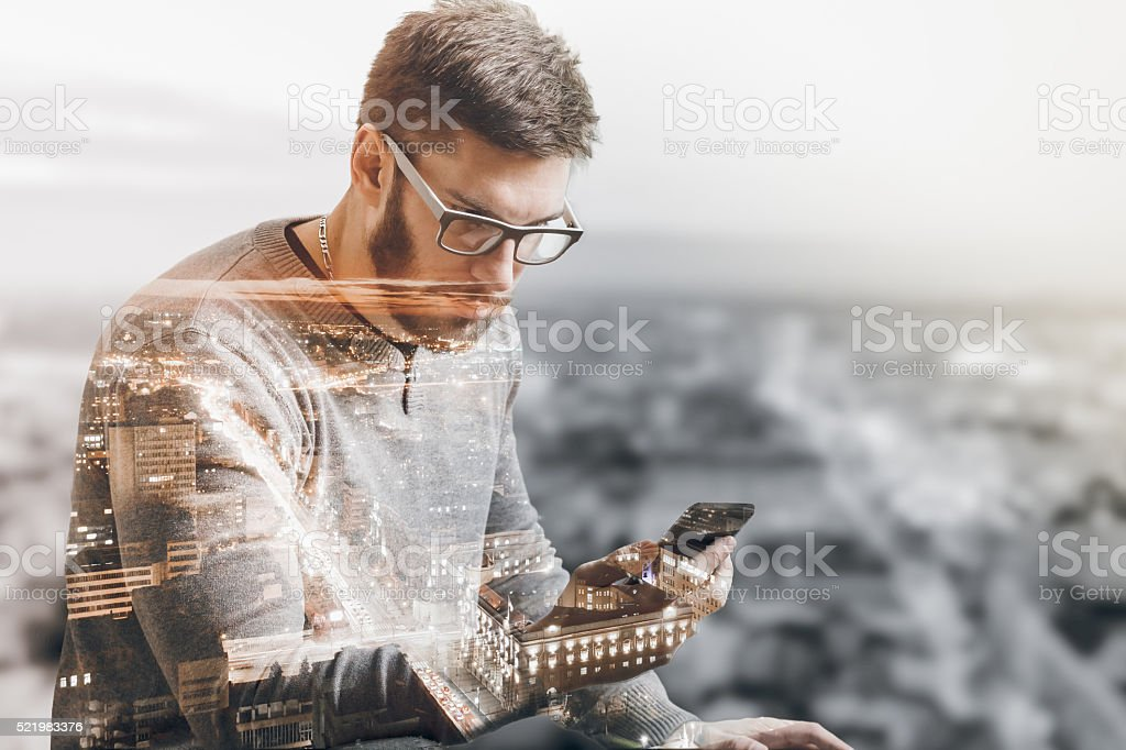 Double exposure of city and man using phone stock photo