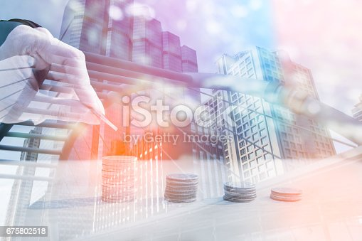 istock Double exposure of city and rows of coins 675802518