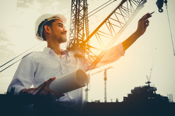 double exposure of civil engineer holding blueprint with construction site. - civil engineer stock photos and pictures