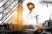 istock Double exposure of civil engineer holding blueprint with construction site. 845537462