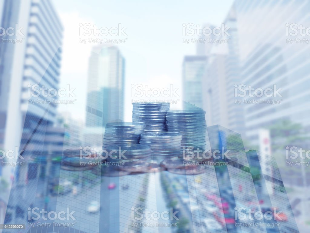 Double exposure of coins and buildings in financial district stock photo