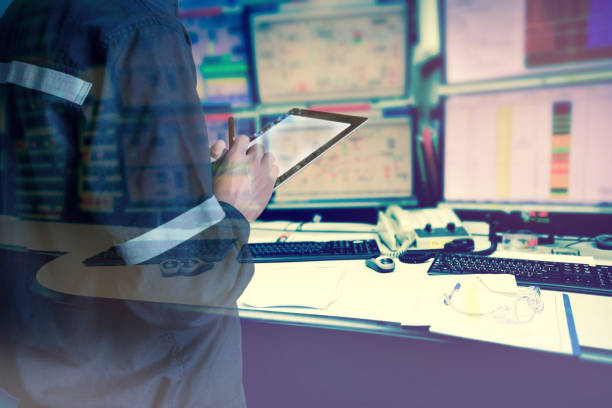Double exposure of  Engineer or Technician man in working shirt  working with tablet in control room of oil and gas platform or plant industrial for monitor process, business and industry concept. stock photo