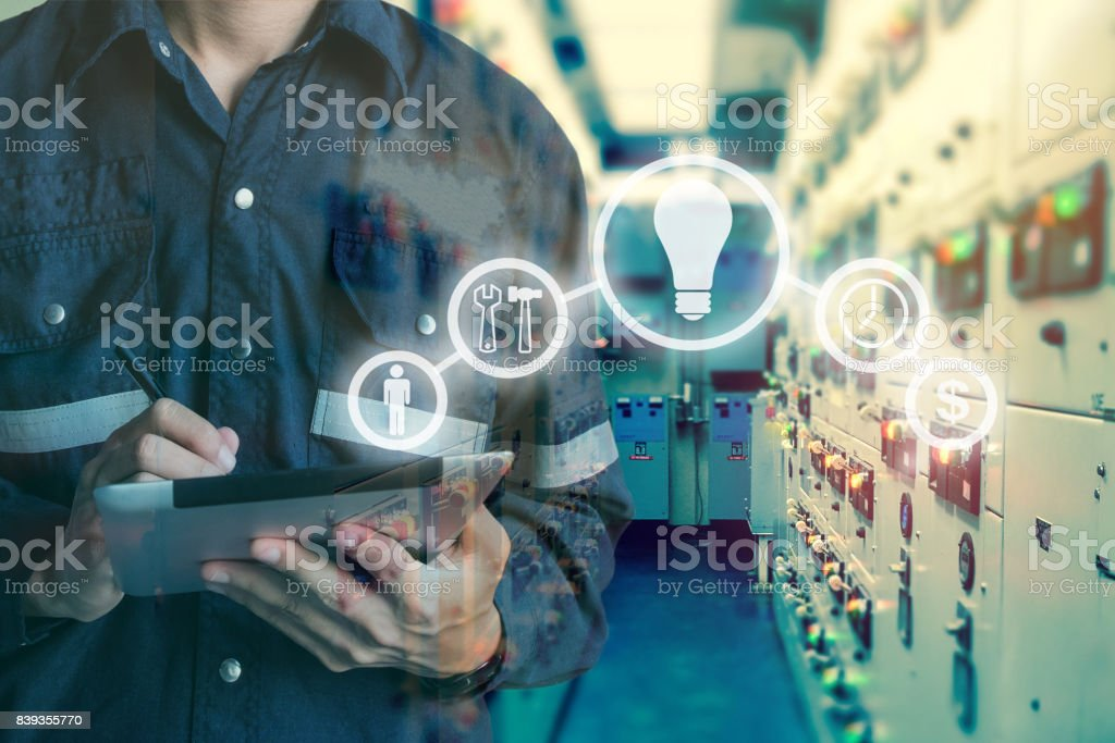 Double exposure of Engineer or Technician man using  tablet in switch gear electrical room oil and gas platform or plant industrial with tools icon, business and electrical industry concept. stock photo